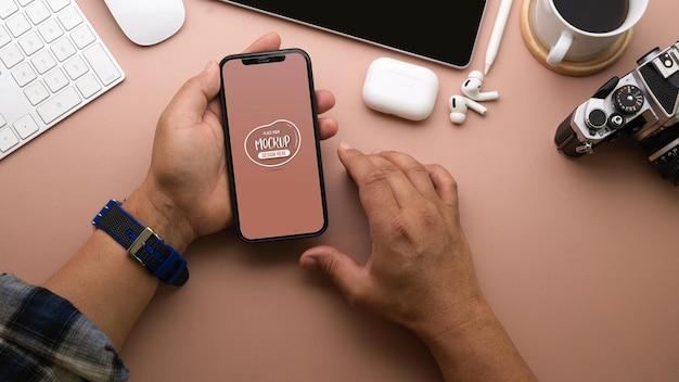 Vista superior das mãos do empresário usando maquete de smartphone