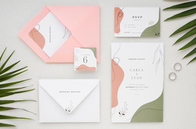 Vista superior de cartões de casamento com anéis e folhas