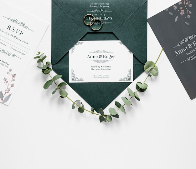 Vista superior de cartões de casamento com anéis e plantas
