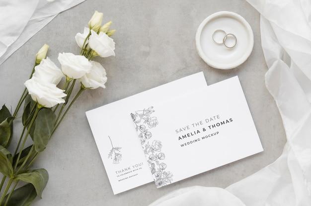 Vista superior de cartões de casamento com anéis e rosas