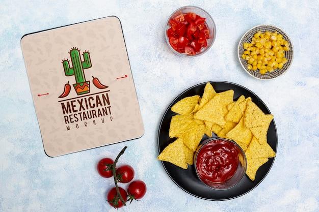 Vista superior de comida de restaurante mexicano com nachos e tomates