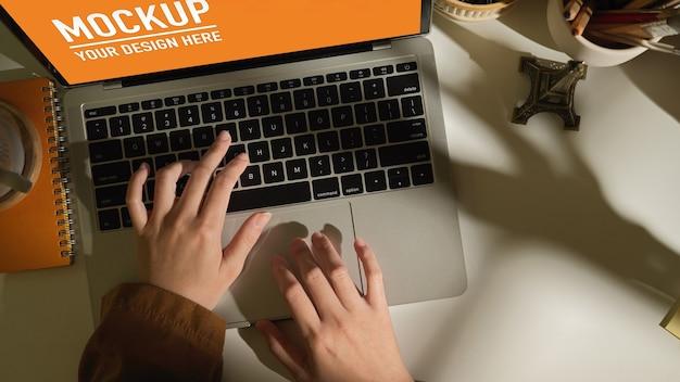 Vista superior de mãos femininas digitando na maquete do laptop na mesa de trabalho branca na sala de home office