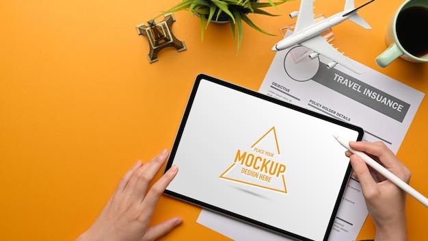 Vista superior de mãos femininas usando com tablet digital para planejar sua viagem de viagem