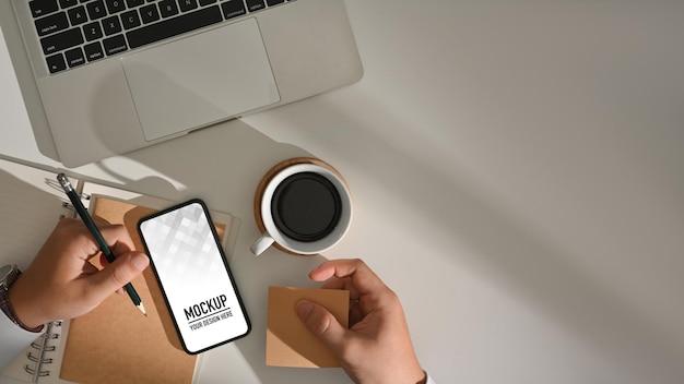 Vista superior de mãos masculinas trabalhando com papelaria e maquete de smartphone