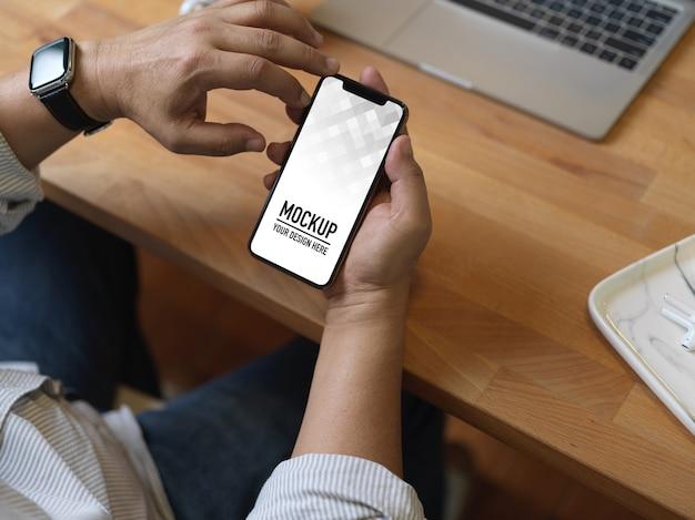 Vista superior de mãos masculinas usando maquete de smartphone na mesa de trabalho de madeira com laptop