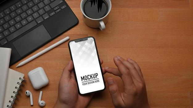 Vista superior de mãos masculinas usando maquete de smartphone