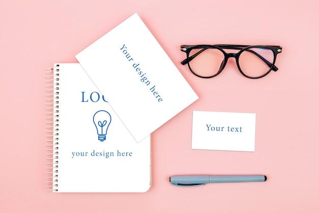 Vista superior de óculos e notebook em fundo rosa, maquete