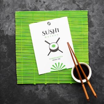 Vista superior de pauzinhos com molho de soja no rolo de bambu para sushi