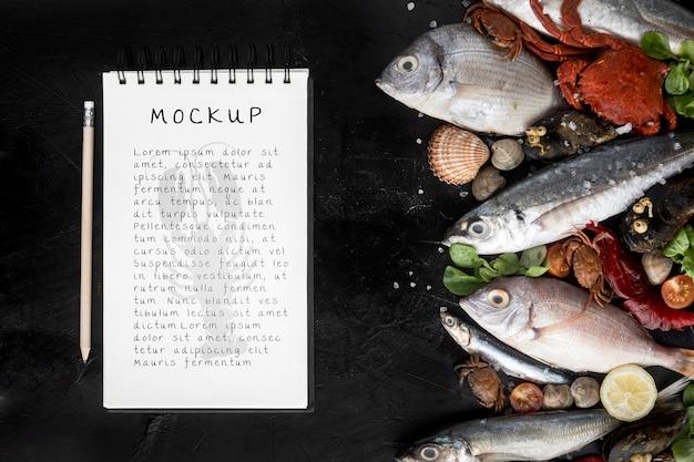 Vista superior de peixes e crustáceos com caderno e caneta