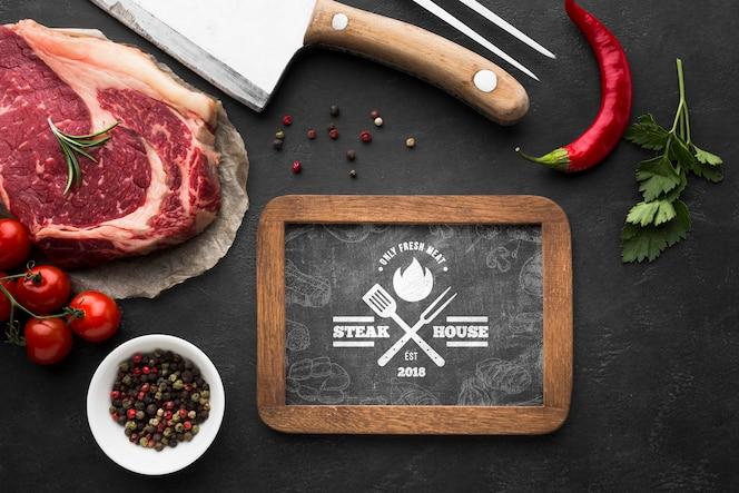 Vista superior de produtos de carne com maquete de lousa