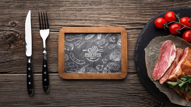 Vista superior de produtos de carne com maquete de quadro-negro