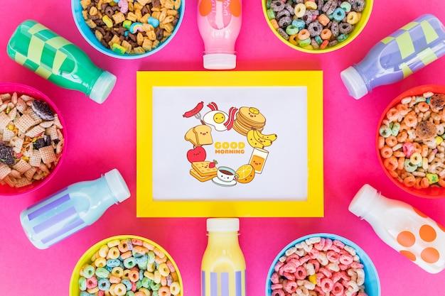 Vista superior de tigelas de cereal e garrafas de leite em fundo rosa