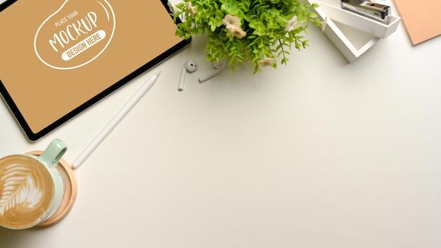 Vista superior de um espaço de trabalho simples com xícara de café, maquete de tablet, suprimentos e vaso