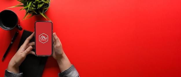 Vista superior de uma jovem segurando uma maquete de smartphone