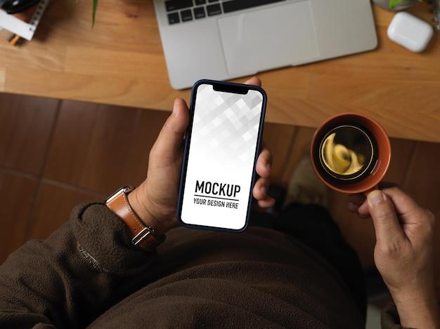 Vista superior de uma mão masculina segurando uma maquete de smartphone