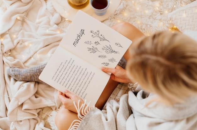 Vista superior de uma mulher lendo uma maquete de livro