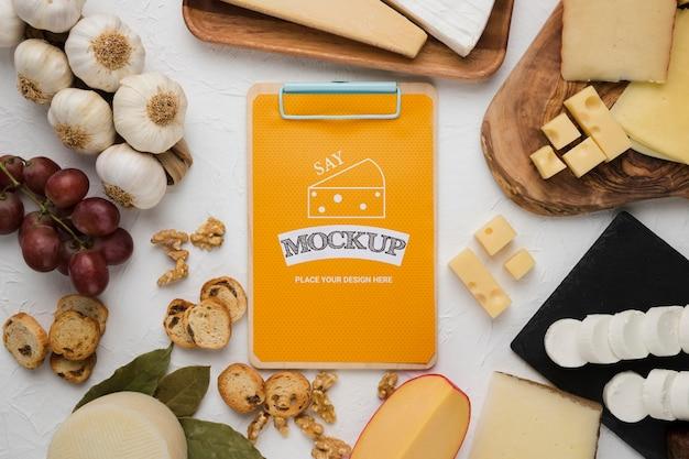 Vista superior de uma variedade de queijo com bloco de notas e alho