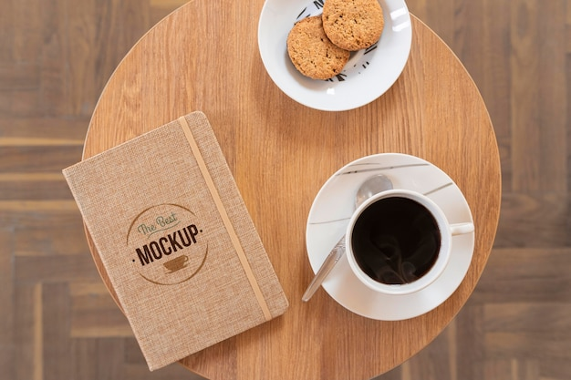Vista superior de uma xícara de café com maquete de notebook