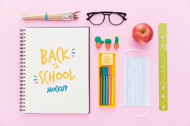 Vista superior de volta ao caderno escolar com maçã e óculos