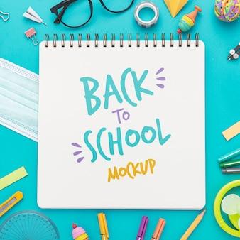 Vista superior de volta ao caderno escolar com óculos e lápis