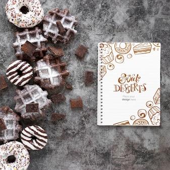 Vista superior de waffles e donuts com notebook