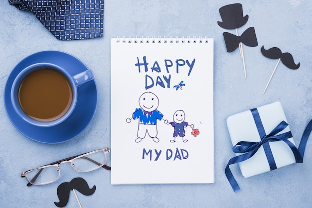 Vista superior do bloco de notas com café e copos para o dia dos pais