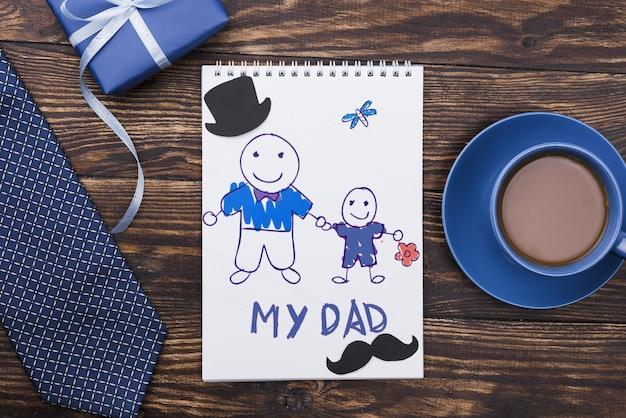 Vista superior do bloco de notas com gravata e presente para o dia dos pais