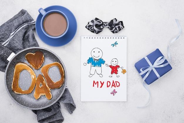 Vista superior do bloco de notas com panquecas na panela e café para o dia dos pais