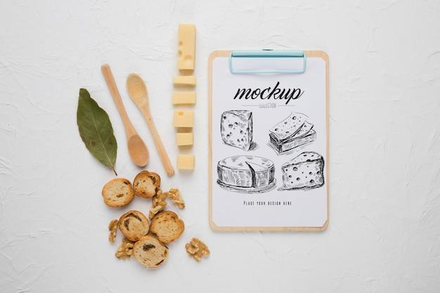 Vista superior do bloco de notas com queijo e colheres