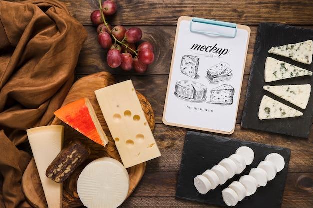 Vista superior do bloco de notas com variedade de queijos e uvas