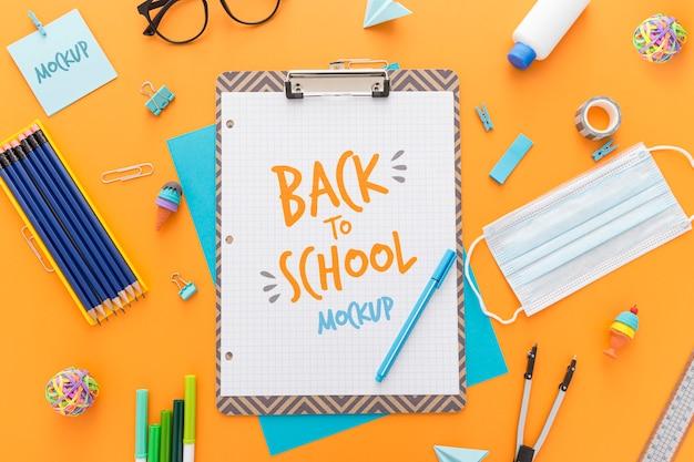 Vista superior do bloco de notas de volta à escola com lápis e itens essenciais