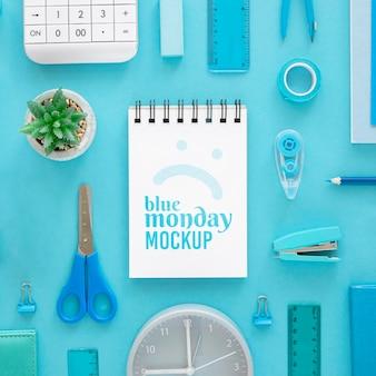 Vista superior do caderno azul de segunda-feira com papelaria e planta
