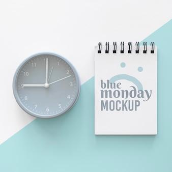 Vista superior do caderno azul de segunda-feira com relógio