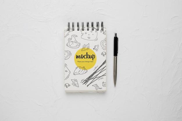 Vista superior do caderno com desenho de queijo e caneta