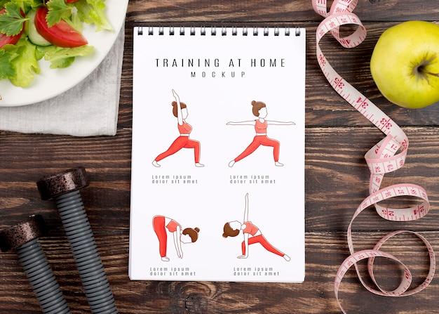 Vista superior do caderno de fitness com pesos e fita métrica