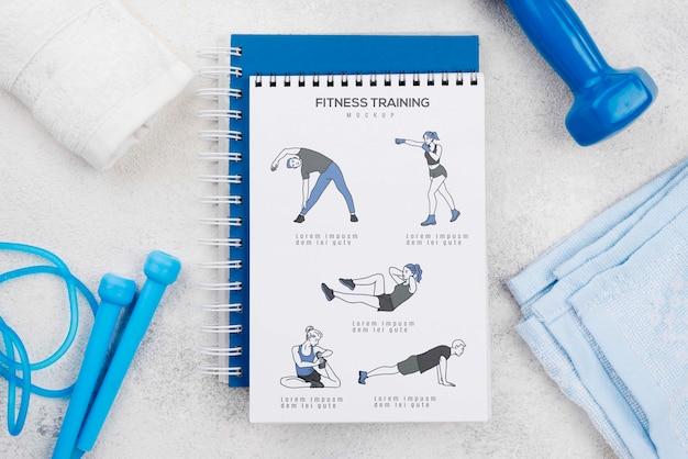 Vista superior do caderno de fitness com pular corda e toalhas