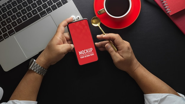 Vista superior do empresário segurando a tela de maquete do smartphone e café