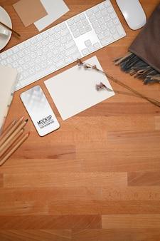 Vista superior do espaço de trabalho com maquete de smartphone, cartão de papel e dispositivo de computador