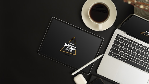Vista superior do espaço de trabalho moderno com simulação de tablet e laptop na mesa preta