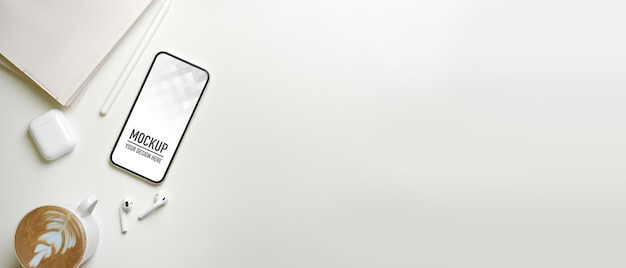 Vista superior do espaço mínimo de trabalho com maquete de smartphone, fone de ouvido, notebook e café