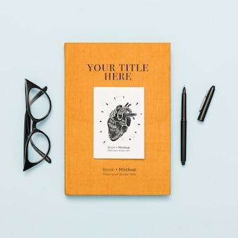 Vista superior do livro com caneta e óculos