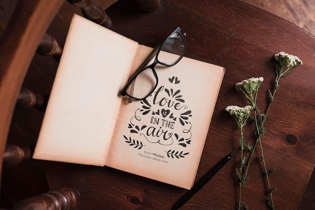 Vista superior do livro com óculos e flores na cadeira