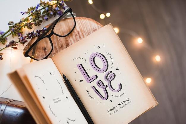 Vista superior do livro com óculos e luzes