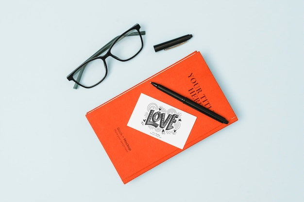 Vista superior do livro com óculos e maquete de caneta