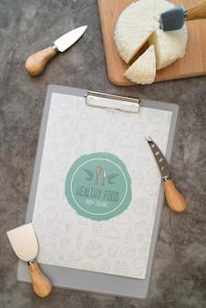 Vista superior do menu com queijo e utensílios