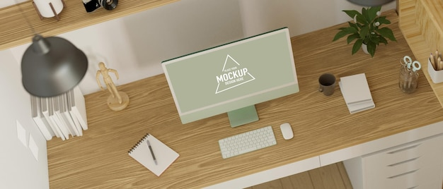 Vista superior do moderno espaço de trabalho projetado com maquete do monitor do computador na mesa de madeira