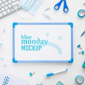 Vista superior do quadro branco de segunda-feira azul com tesouras e papelaria