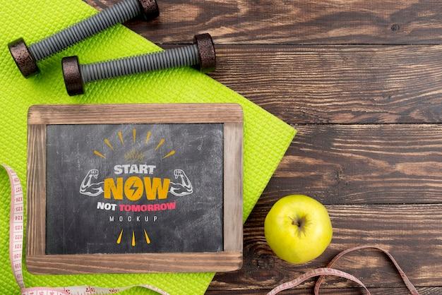 Vista superior do quadro de fitness com maçã e pesos