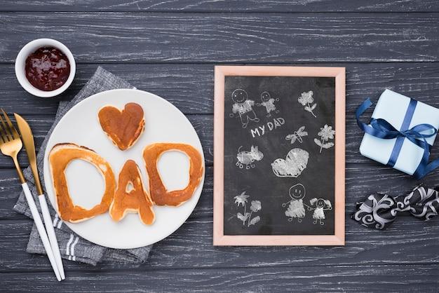 Vista superior do quadro-negro com panquecas e muffin para dia dos pais