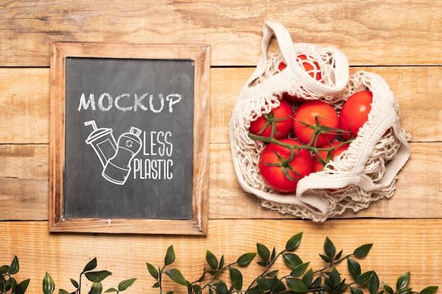 Vista superior do quadro-negro e tomates em uma sacola reutilizável